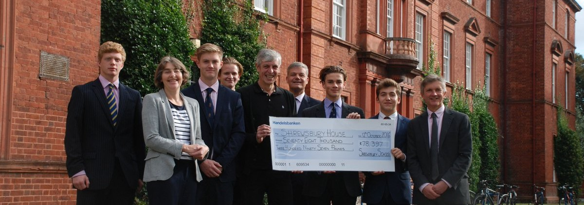 Dave Brereton receiving the cheque from the Head of Shrewsbury School, Mark Turner, teacher Leslie Drew and members of the 6th form